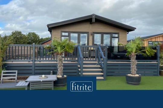 front view of holiday lodge with decking and astroturf
