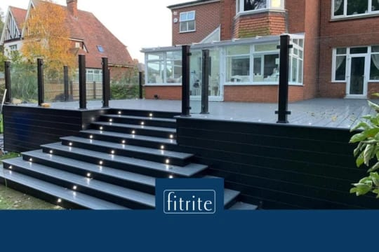 large decking area around house with steps, lighting and glass balustrading